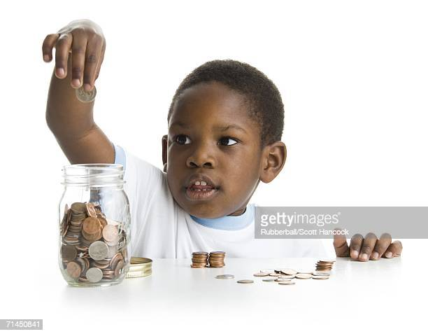Close-up of a boy collecting coins in a jar
