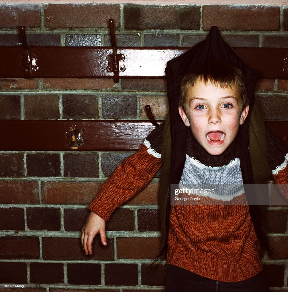 close-up of a boy (6-8) hanging by his sweater on a clothes hook : Stock Photo