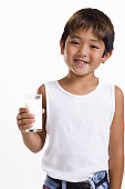 Close-up of a boy holding a glass of milk