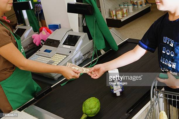 Close-up of a boy paying cash at the checkout counter at a store