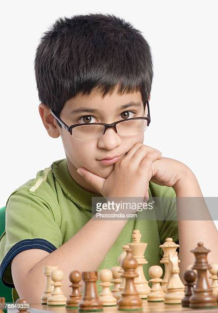 Close-up of a boy playing chess with his hand on his chin