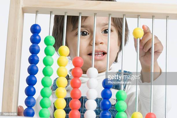 Close-up of a boy playing with an abacus