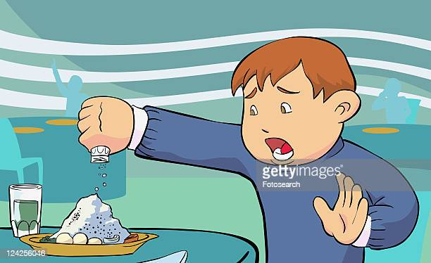 Close-up of a boy pouring salt on food