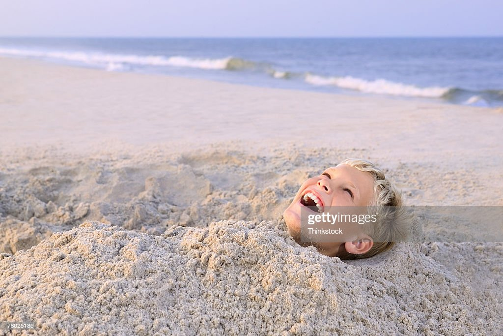 Close-up of a boy screaming and laughing while buried in the sand at the beach