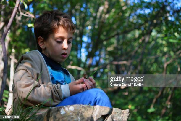 Close-Up Of A Boy Sitting Outdoors