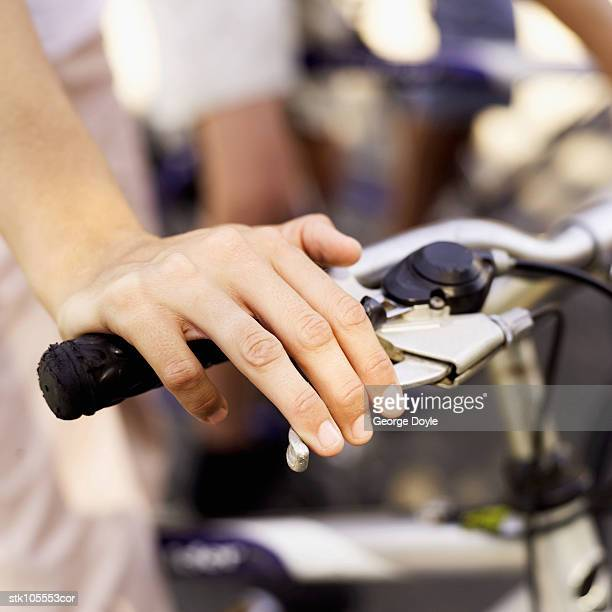 Close-up of a boy's hand on a cycle handle bars
