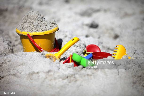 A close-up of a bucket and shovel in the sand of a beach