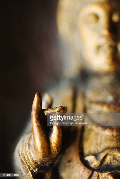 Close-up of a Buddha sculpture in meditation pose with fingers in 'ohm' position.