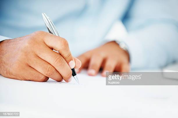 Close-up of a business man writing on paper