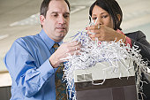 Close-up of a businessman and a Hispanic businesswoman looking at shredded papers