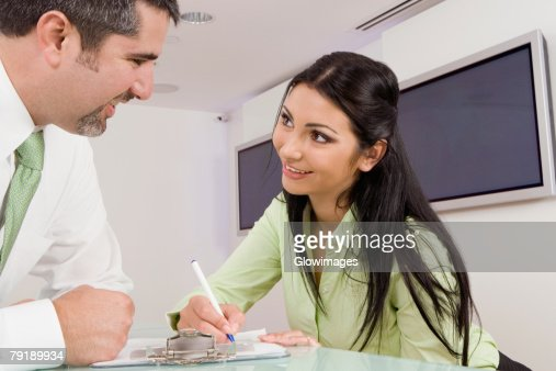 Close-up of a businessman and a receptionist looking at each other and smiling : Foto de stock