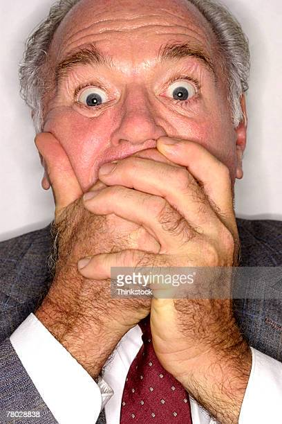 Close-up of a businessman covering his mouth in surprise as he looks at the viewer.