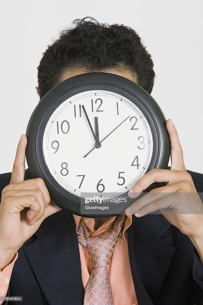 Close-up of a businessman hiding his face with a clock : Foto de stock
