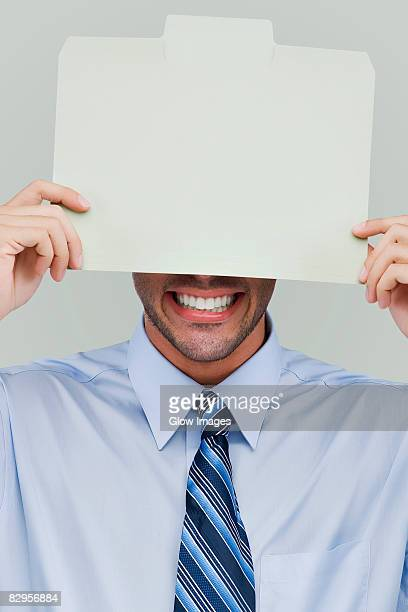 Close-up of a businessman holding a placard in front of his face
