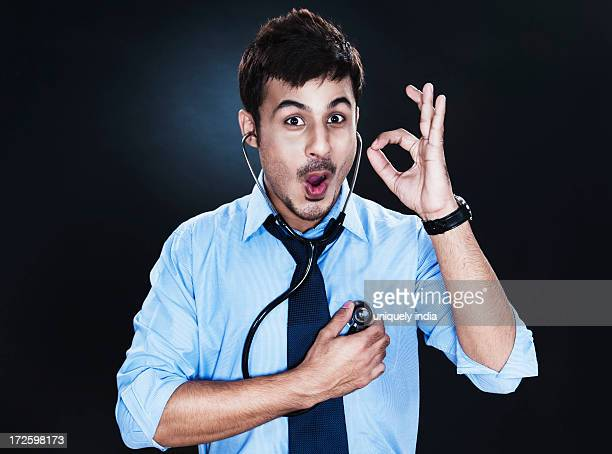 Close-up of a businessman listening to his heartbeat with stethoscope and showing ok sign
