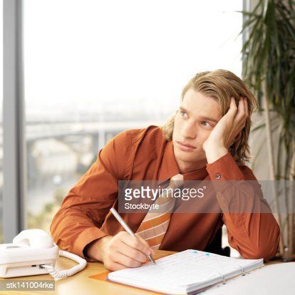 close-up of a businessman sitting in office looking bored : Stock Photo
