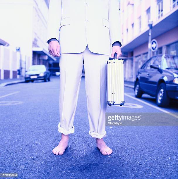 Close-up of a businessman standing barefoot with a briefcase