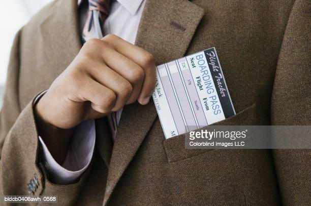 Close-up of a businessman's hand removing a boarding pass from a jacket pocket