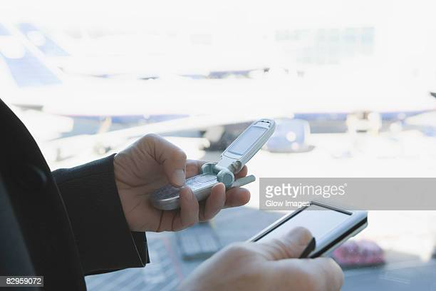 Close-up of a businessman's hands using a mobile phone and a personal data assistant