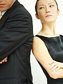 Close-up of a businesswoman and a businessman back to back