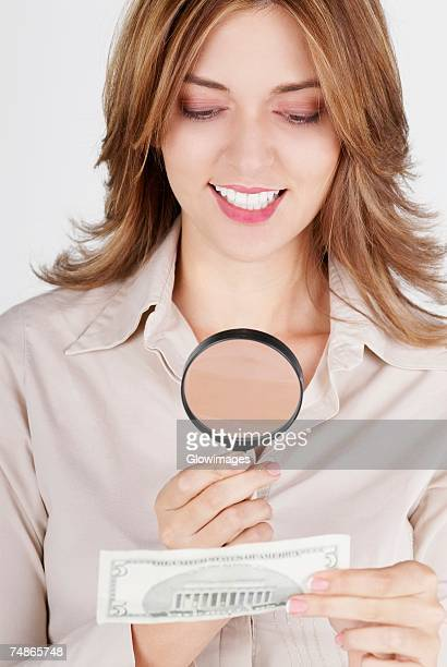 Close-up of a businesswoman examining a dollar bill with a magnifying glass and smiling