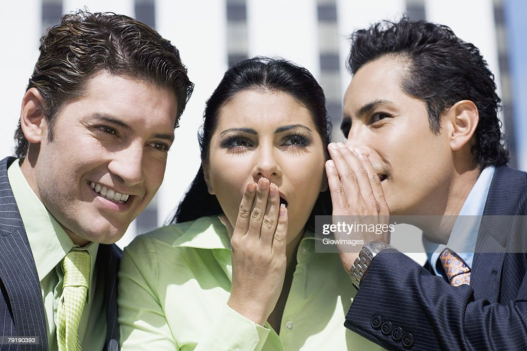 Close-up of a businesswoman gossiping with two businesswomen : Stock Photo