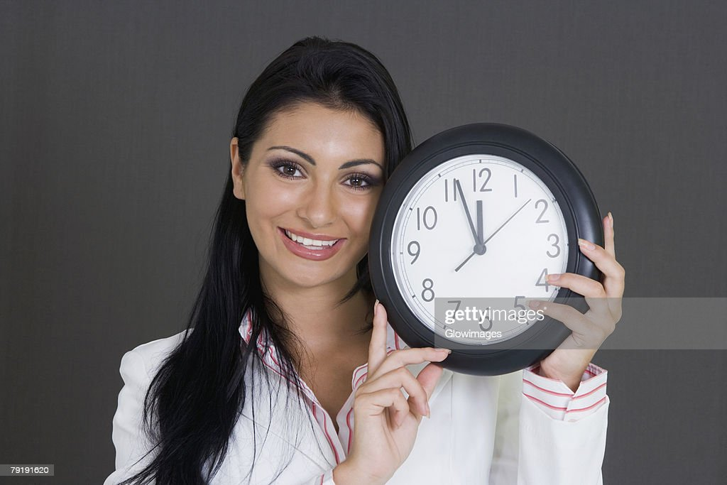 Close-up of a businesswoman holding a clock and smiling : Foto de stock