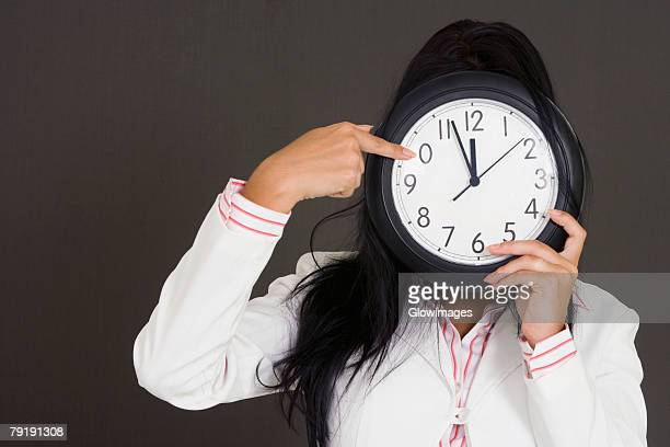 Close-up of a businesswoman holding a clock in front of her face and pointing
