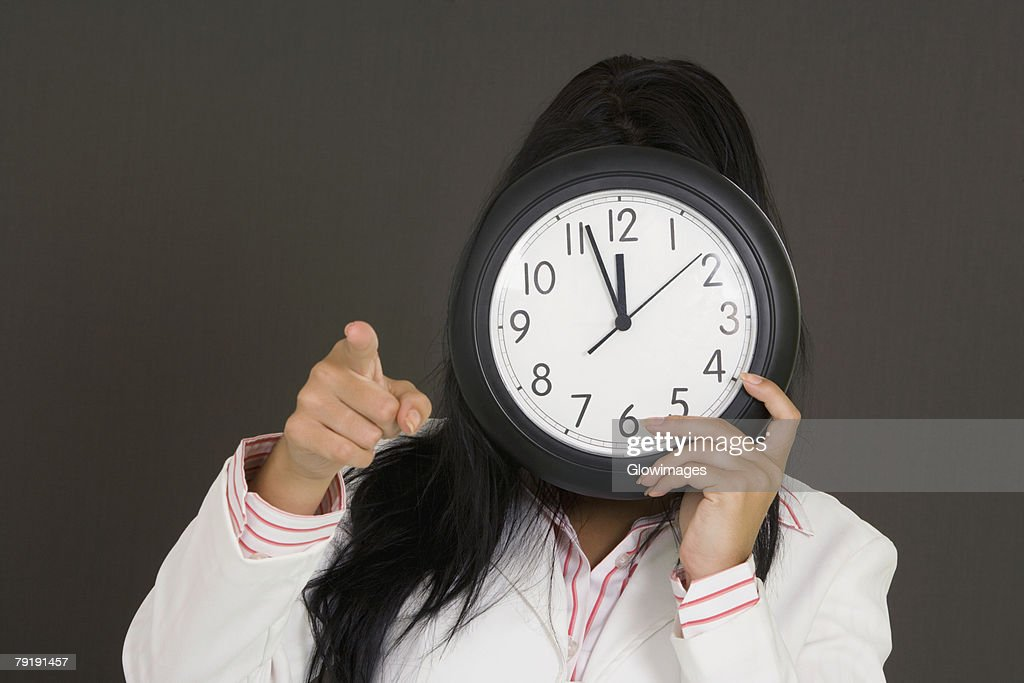 Close-up of a businesswoman holding a clock in front of her face and pointing : Foto de stock