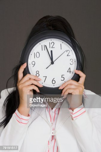 Close-up of a businesswoman holding a clock in front of her face : Foto de stock