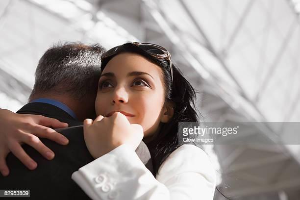 Close-up of a businesswoman hugging a businessman