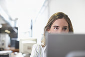 Close-up of a businesswoman looking at a laptop in an office