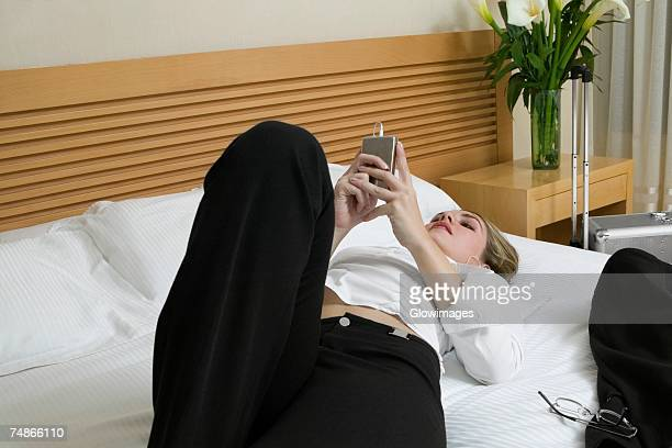 Close-up of a businesswoman lying on the bed listening to an MP3 player