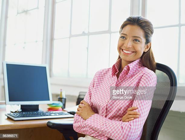close-up of a businesswoman sitting in front of a computer with her arms crossed