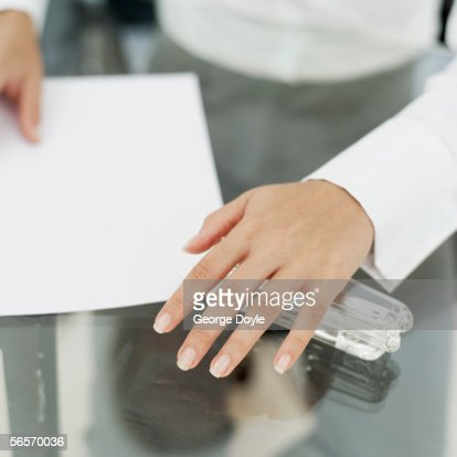 close-up of a businesswoman stapling paper