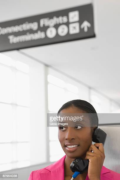 Close-up of a businesswoman talking on a pay phone and smiling