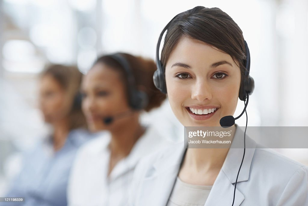 Closeup of a call center employee with headset at workplace : Stock Photo