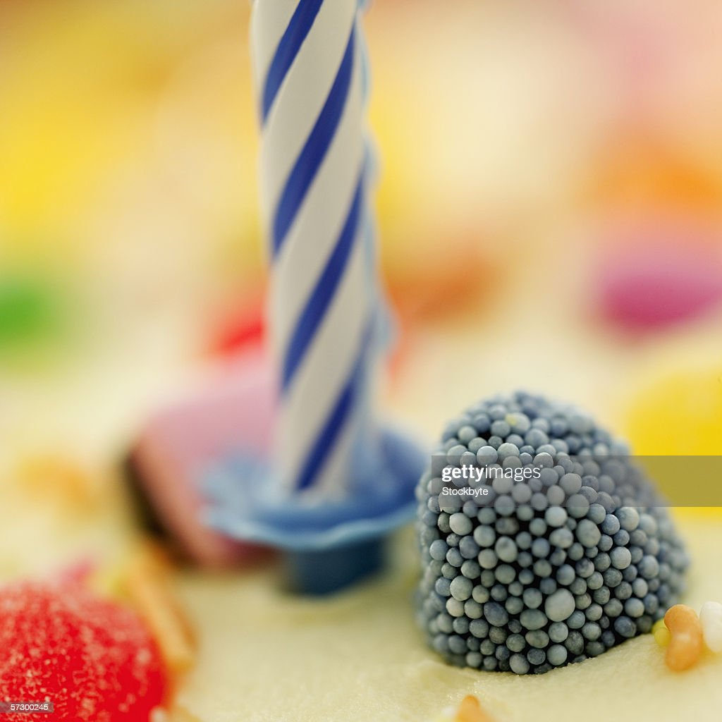 Close-up of a candle on a birthday cake : Stock Photo
