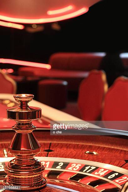 Close-up of a casino roulette table with blurred chairs