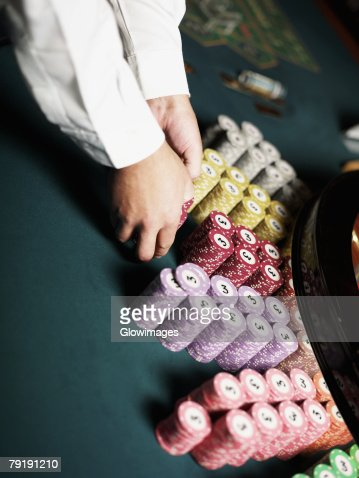Close-up of a casino worker's hand arranging gambling chips on a gambling table : Foto de stock
