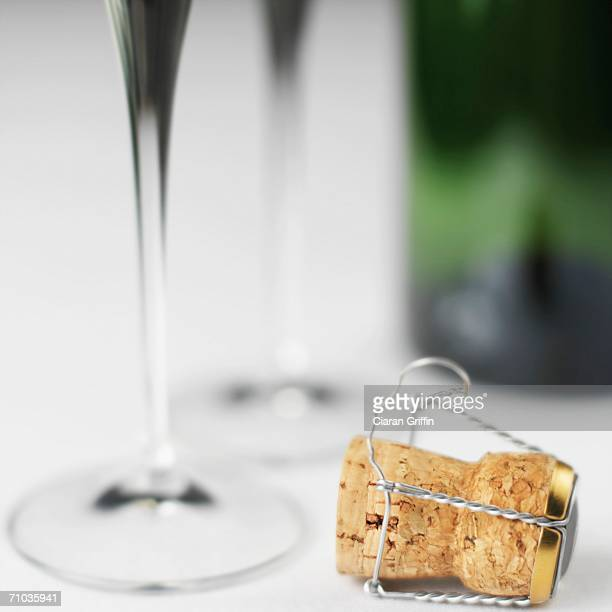 Close-up of a champagne cork with champagne flutes and bottle in the background