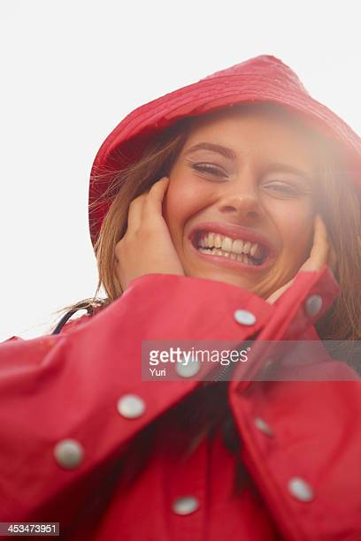 Closeup of a cheerful female in a red raincoat hat outdoors