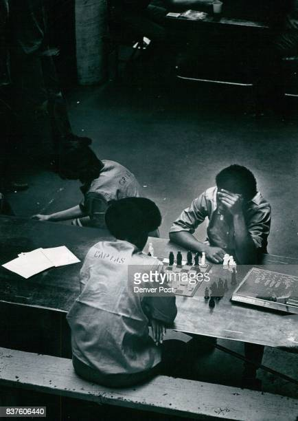 Closeup of a Chess Game in the Denver County Jail Cellblock Area Word 'capias' an uniform indicates the man is awaiting trail as are others in Photo...