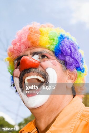 Close-up of a circus clown with a red nose and laughing : Stock Photo