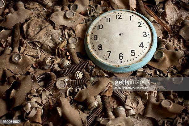 Close-up of a clock on the heap of gas masks,