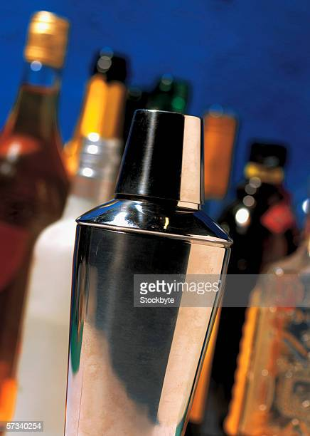 close-up of a cocktail shaker with bottles behind (blurred)