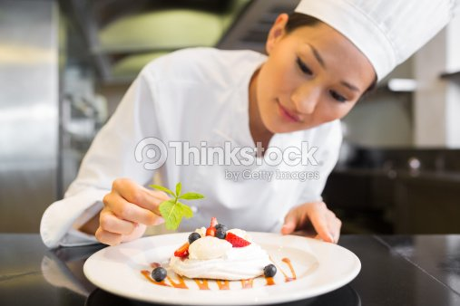 Concentrated female chef garnishing food in kitchen stock for Cuisinier 71