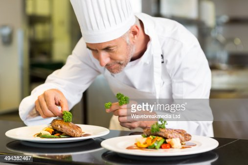 Concentrated male chef garnishing food in kitchen : Stock-Foto