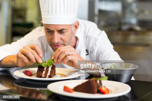 Concentrated male pastry chef decorating dessert in kitchen : Stock Photo