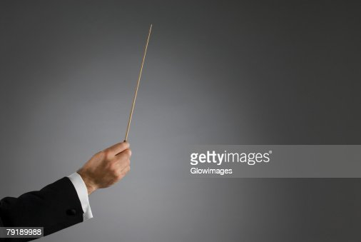 Close-up of a conductor's hand holding a conductor's baton : Foto de stock